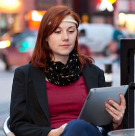 Une femme utilisant sa tablette avec le Muse posé sur sa tête.